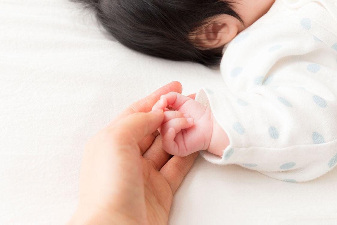 mom holding newborn baby hand