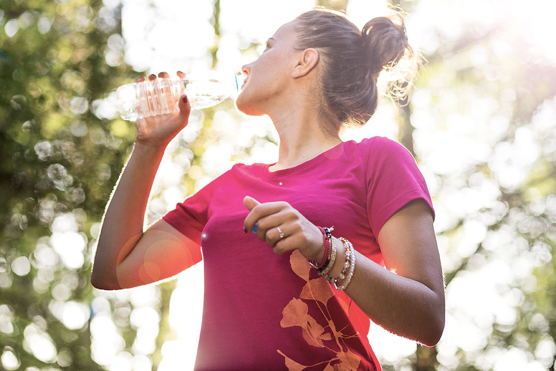 mother drinking from water bottle while running in nature